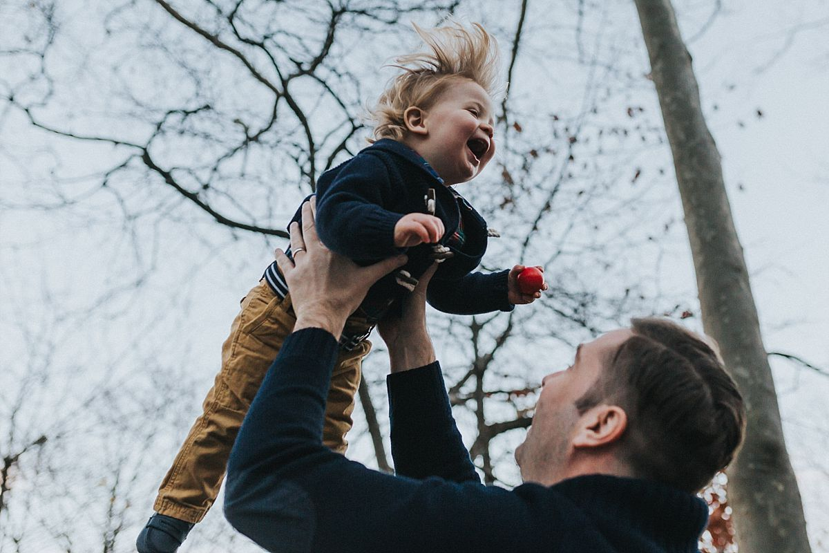 nyc family and newborn photographer dad throws toddler in air for fun while in nyc park