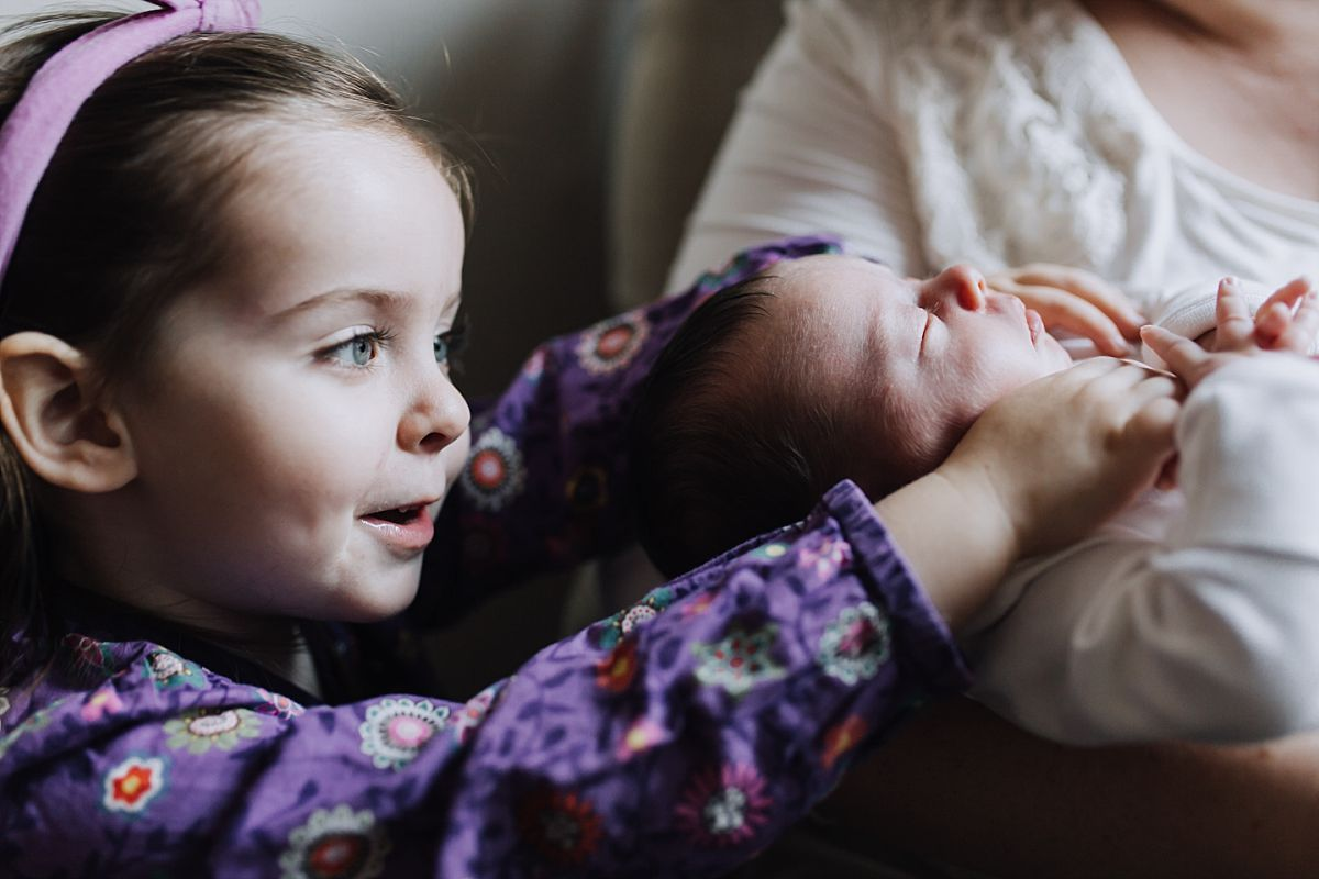 nyc family and newborn photographer big sister leans over to cuddle newborn sister for in home family session