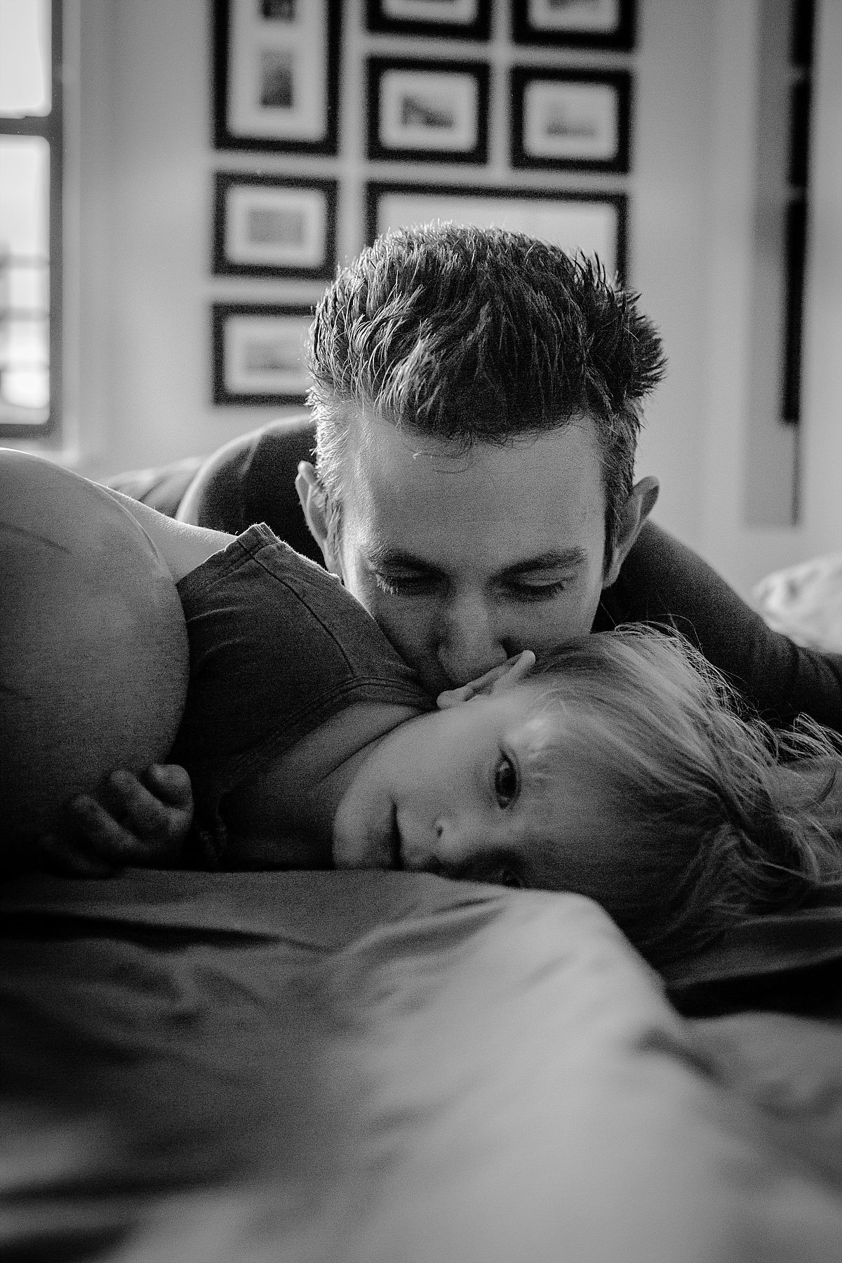 nyc family and newborn photographer dad playing with son on bed at in home family session