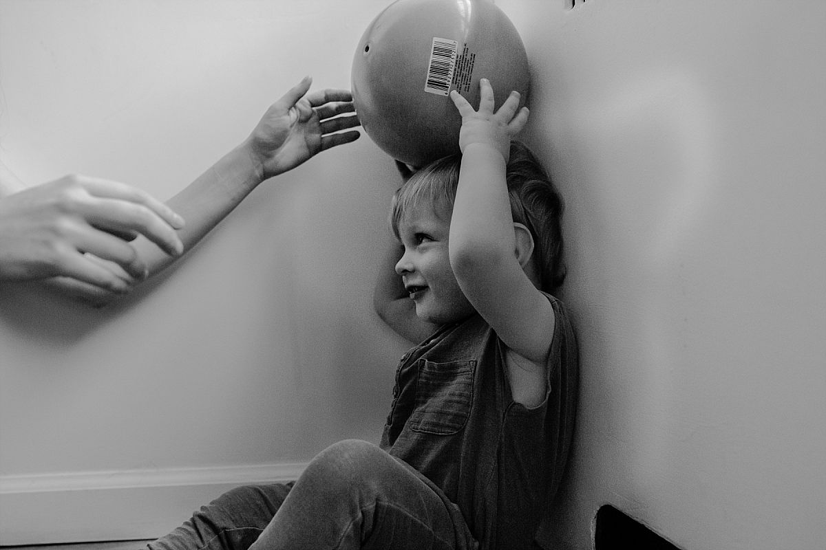 nyc family and newborn photographer toddler son leans against wall with ball over his head