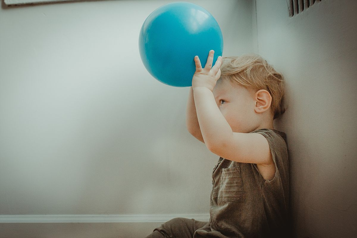 nyc family and newborn photographer son plays with blue blue ball against white wall