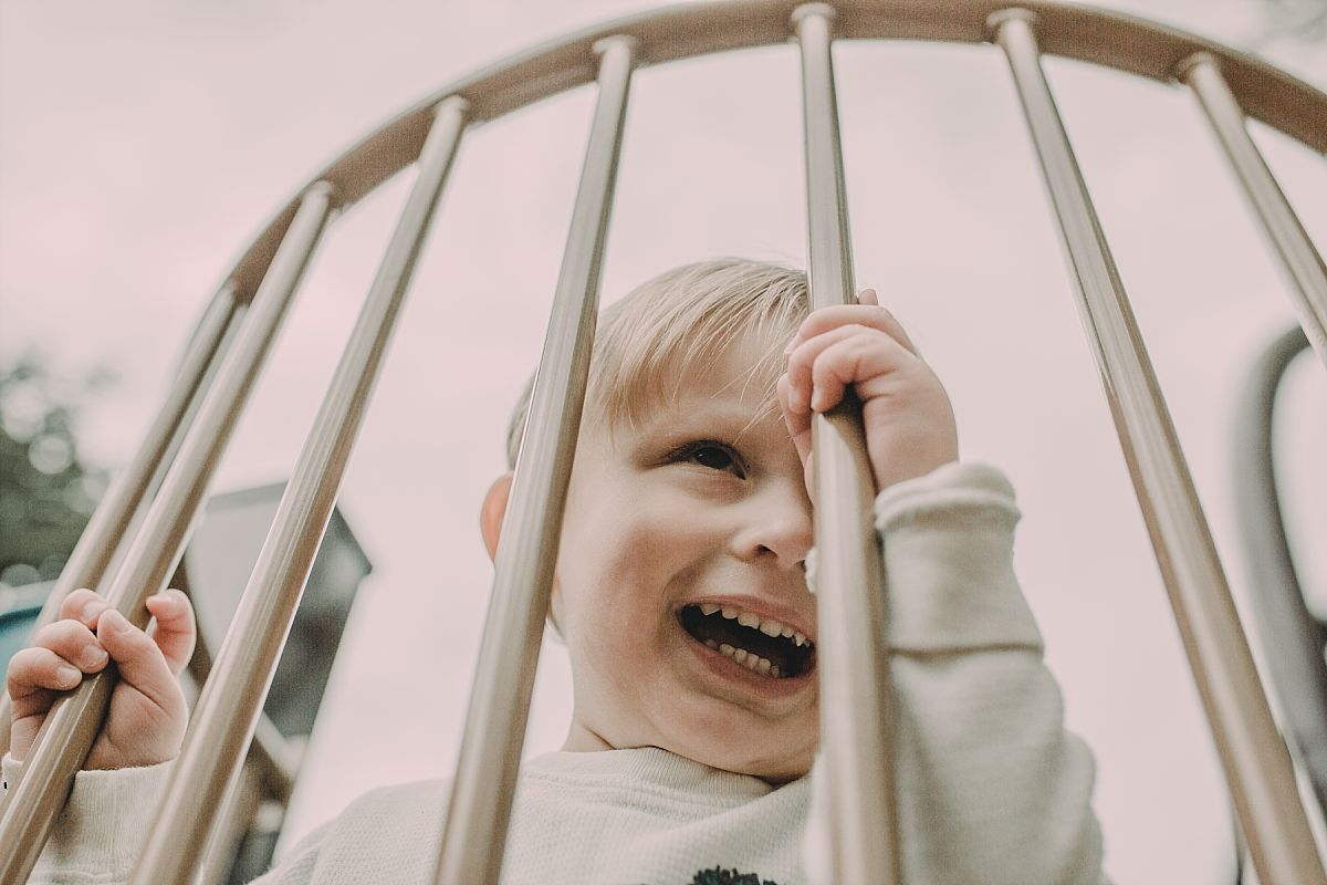 nyc family and newborn photographer boy plays looking through playground bars laughing