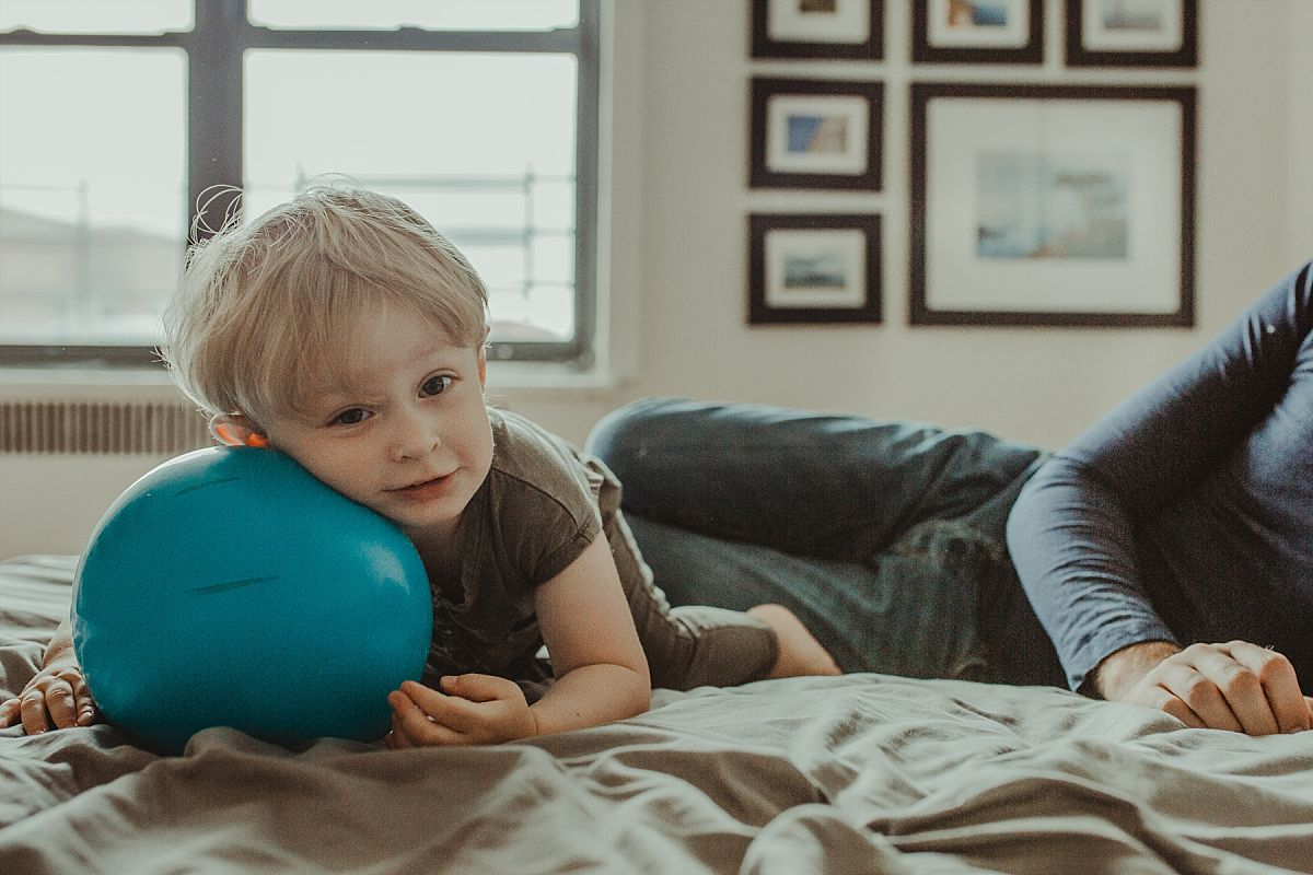 nyc family and newborn photographer boy plays with big blue ball on parents bed in nyc apartment