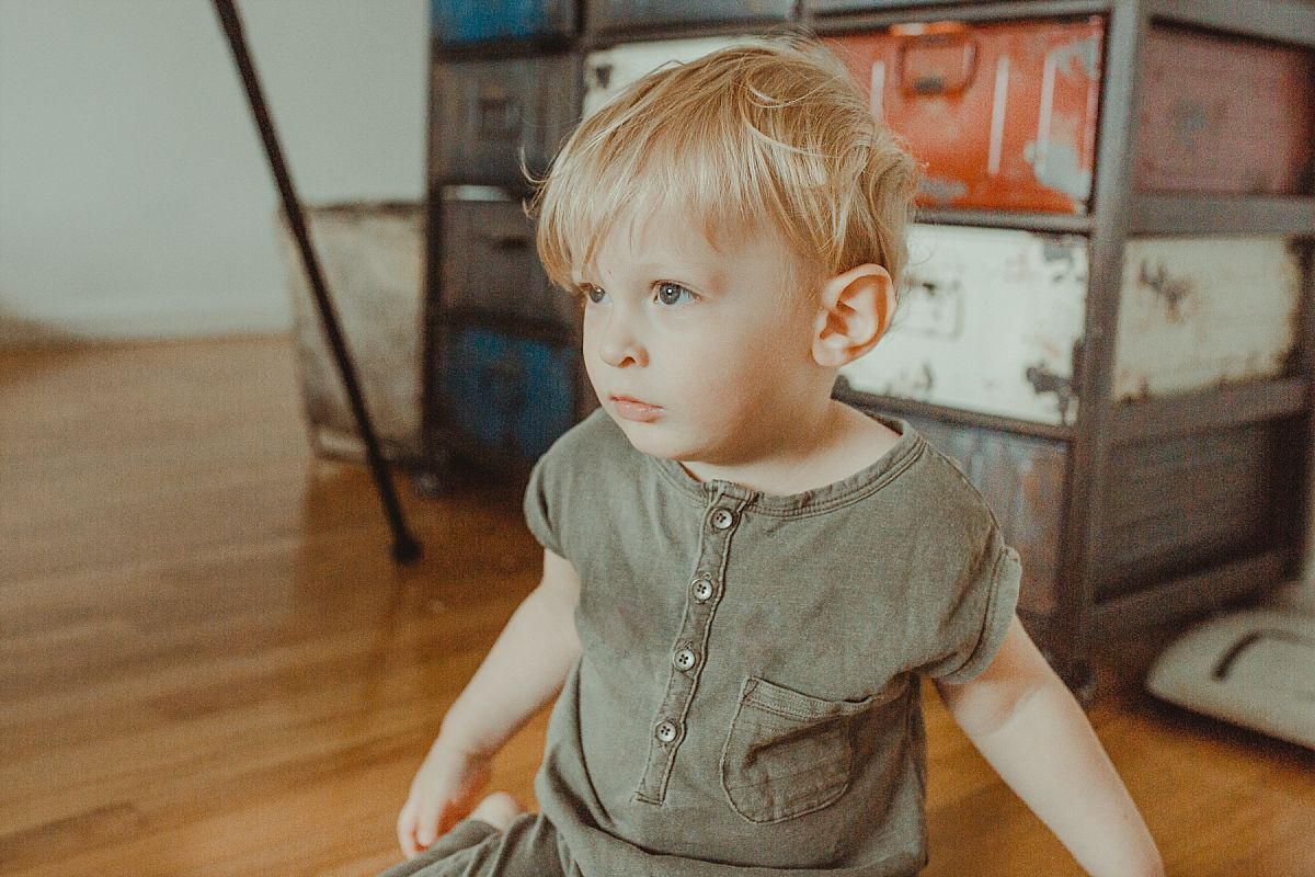 nyc family and newborn photographer boy sits in front of industrial chester drawers in bedroom