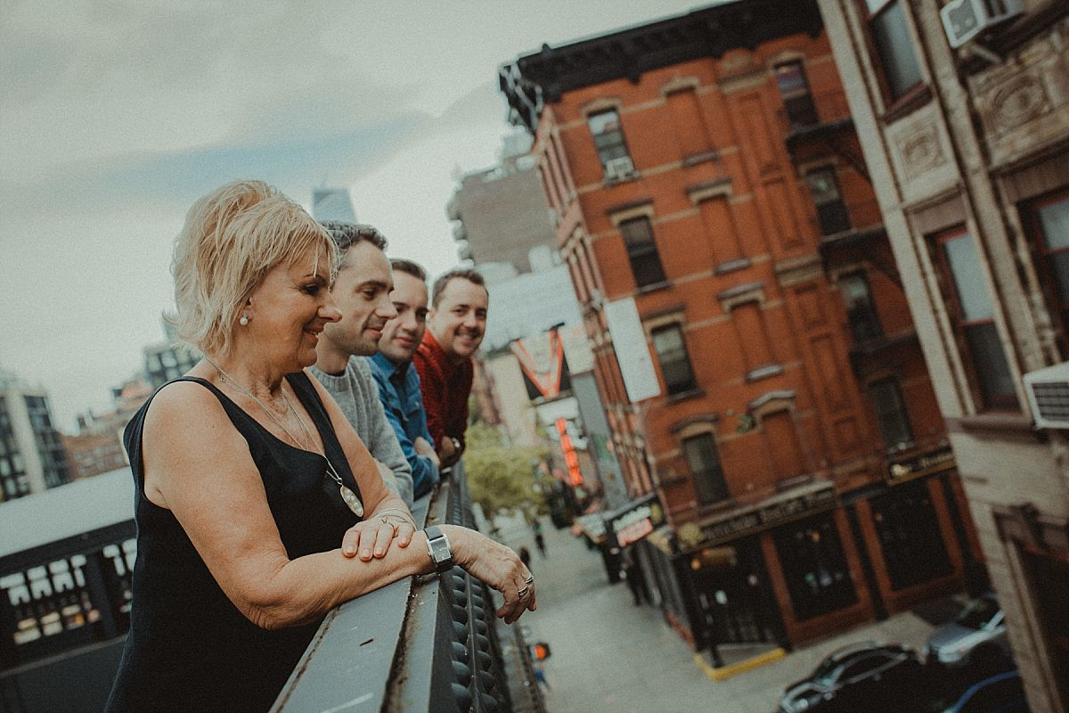 mom with three sons leaning over railing and looking at road at the high line in nyc by Krystil McDowall photography