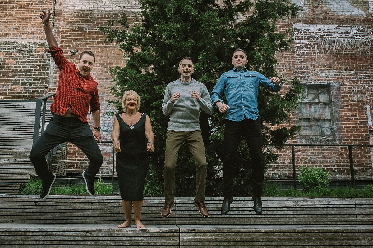 mom and three sons in the air jumping off park bench during lifestyle family photo session in nyc