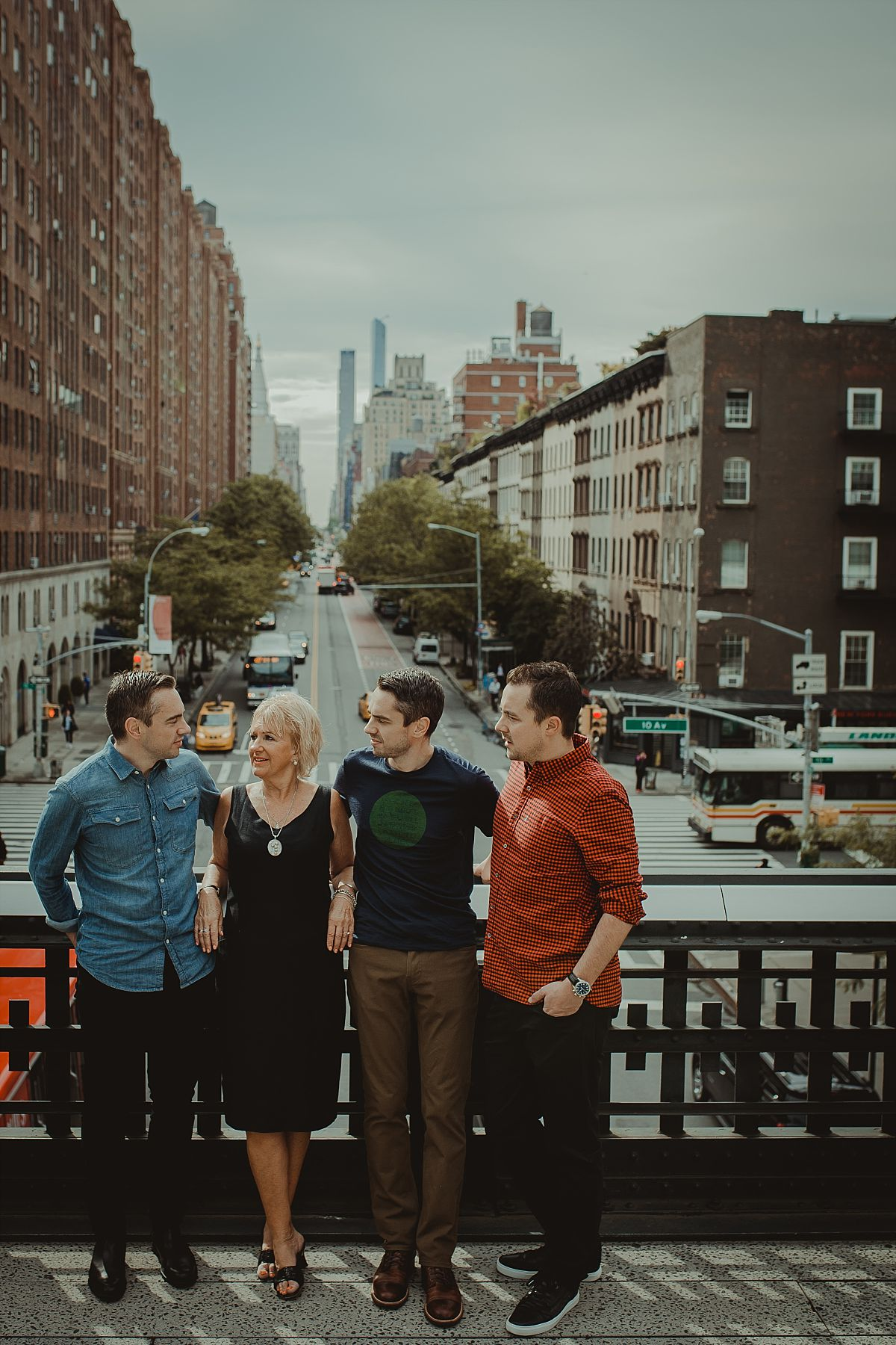 mom and three sons on bride at the highline overlooking busy nyc streets in nyc family photo session