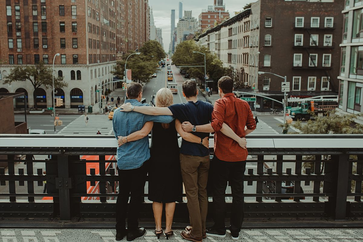 mom and three sons on bride at the highline overlooking busy nyc streets in nyc family photo session photo taken from behind with arms wrapped around each other
