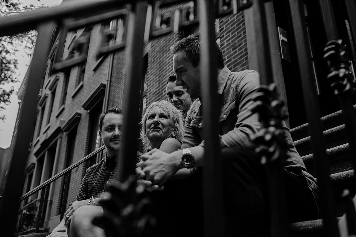 mom and three sons sitting on nyc stoop in chelsea and peaking through stoop rails in nyc family photo session