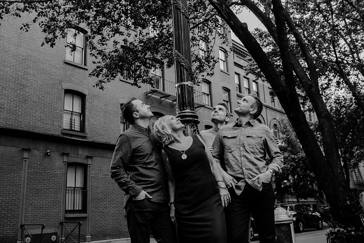 mom and three sons looking up at street sign in chelsea during nyc family photo session. photo by krystil mcdowall photography