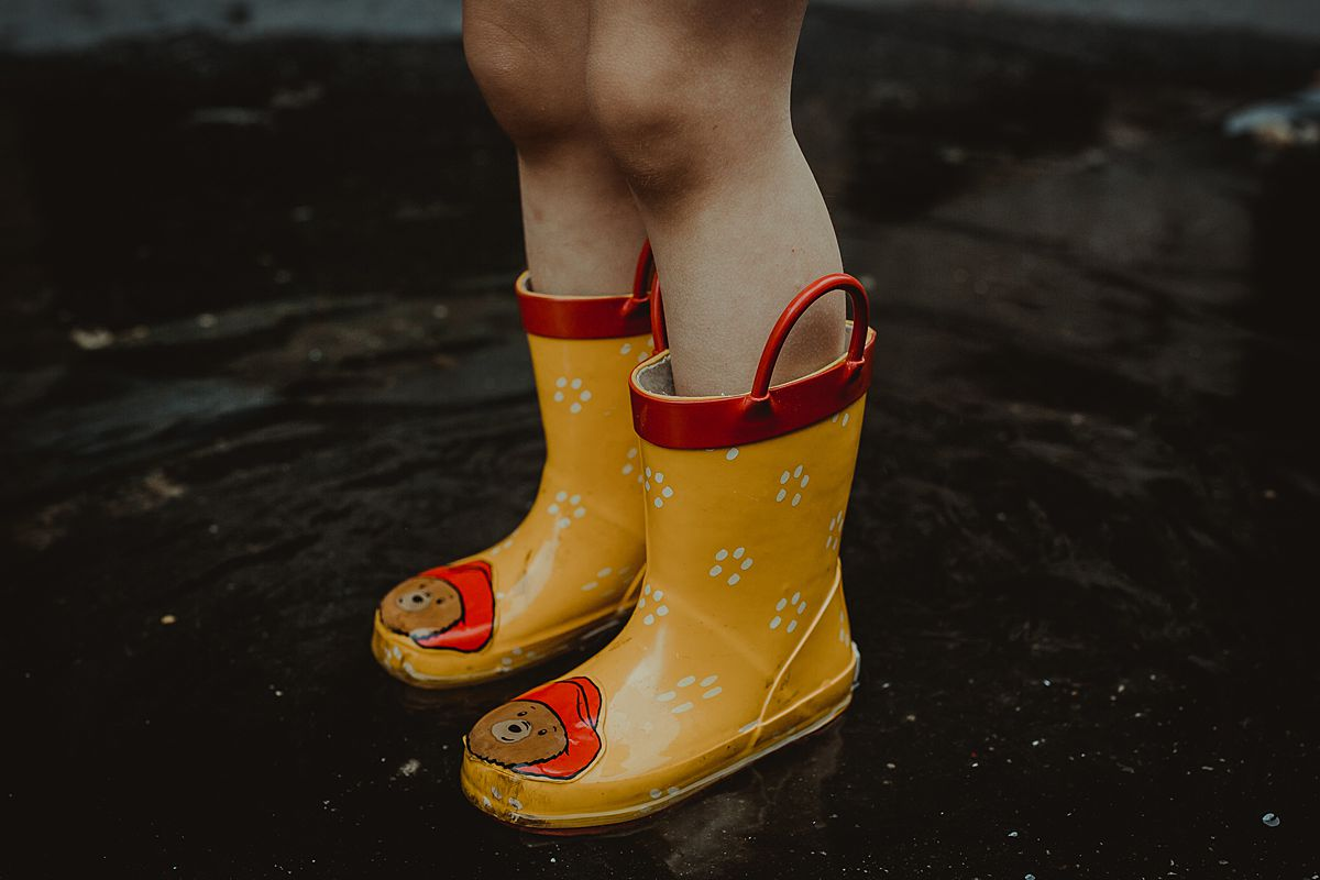 daughter's yellow rainboots that have paddington bear. photo taken while toddler stands in puddle