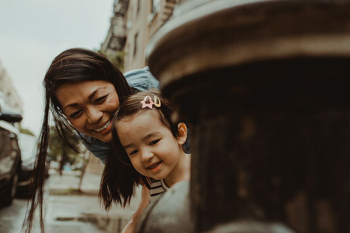 mom and daughter peek around fire hydrant on side of nyc street. capturing family moments and life nyc family and newborn photographer krystil mcdowall