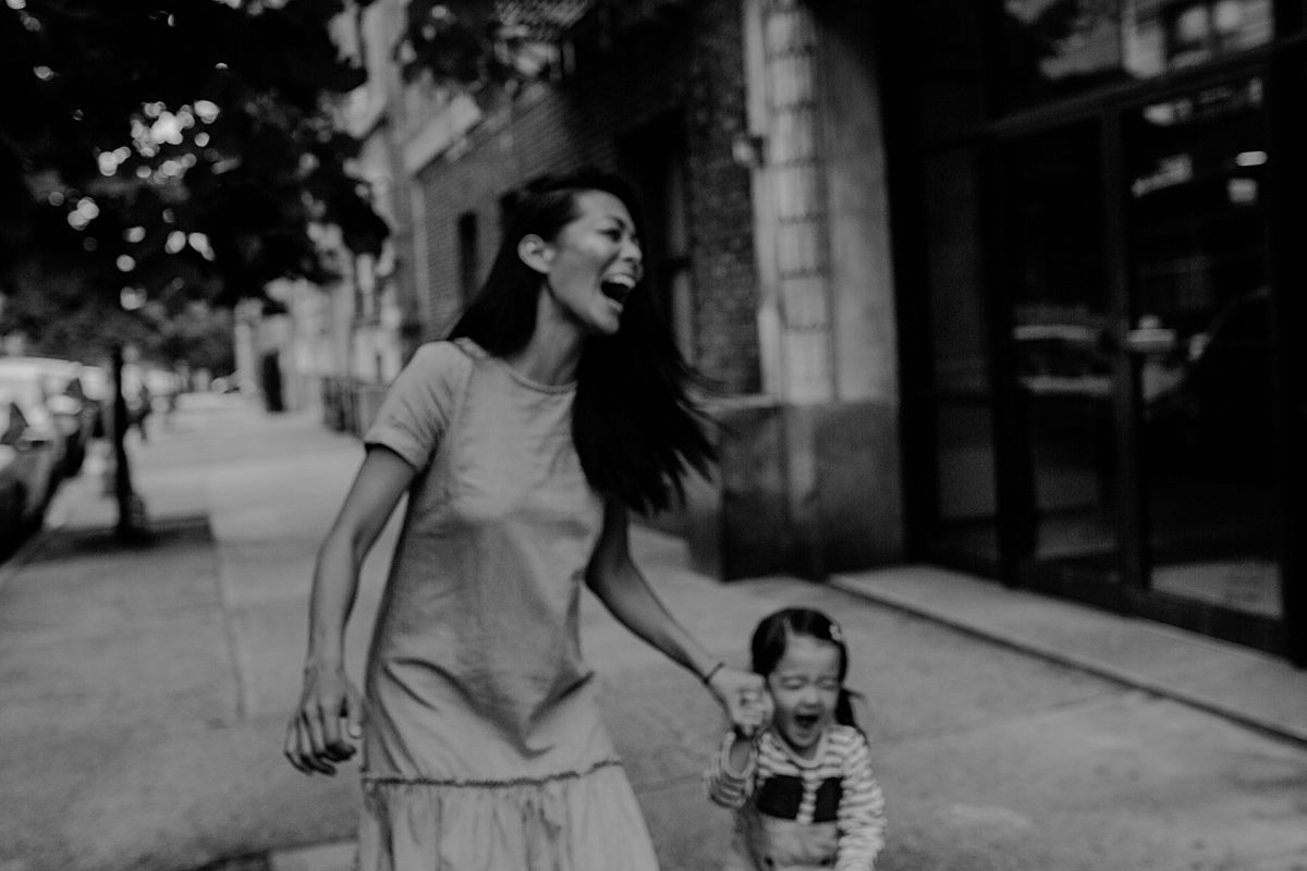 the hugest laughs from mom and daughter while in nyc sidewalk. photo by nyc family photographer