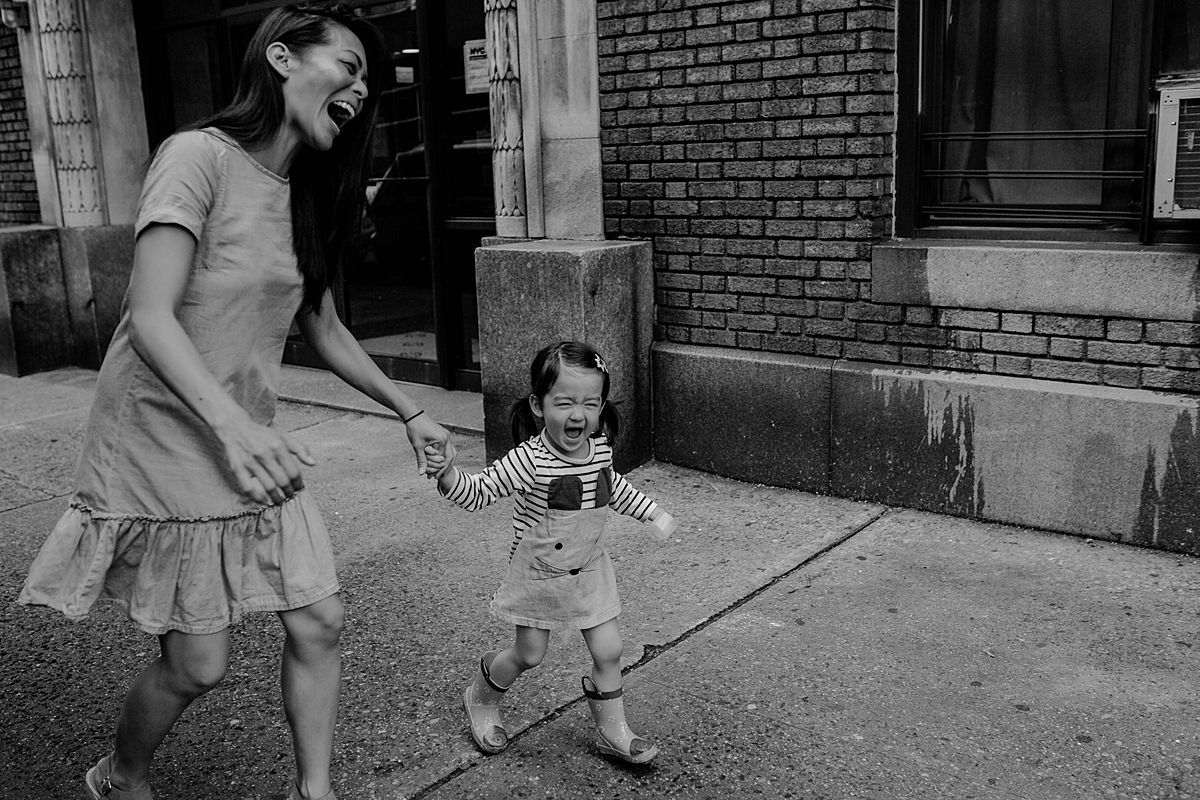 mom and daughter walk along nyc streets of Manhattan laughing heaps and holding hands. nyc family and newborn photographer. photo by krystil mcdowall