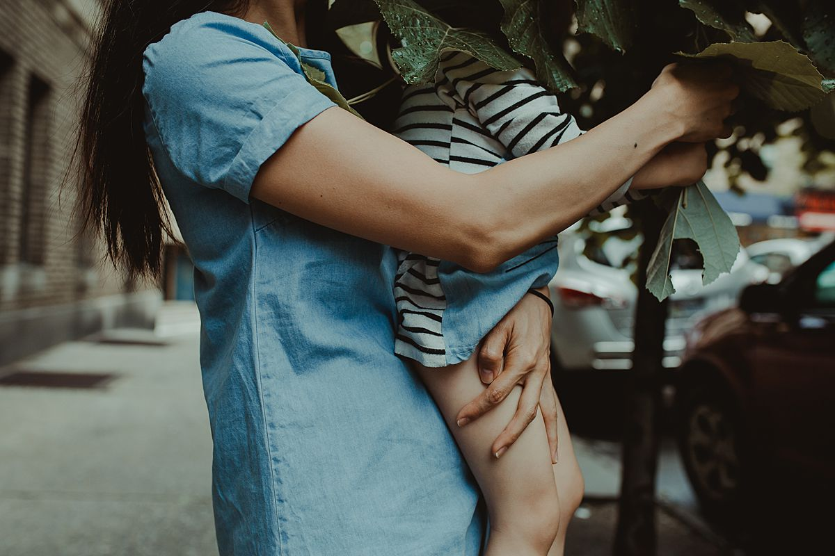 mom holding daughter so she can play with tree leaves. documentary lifestyle session by nyc family and newborn photographer krystil mcdowall