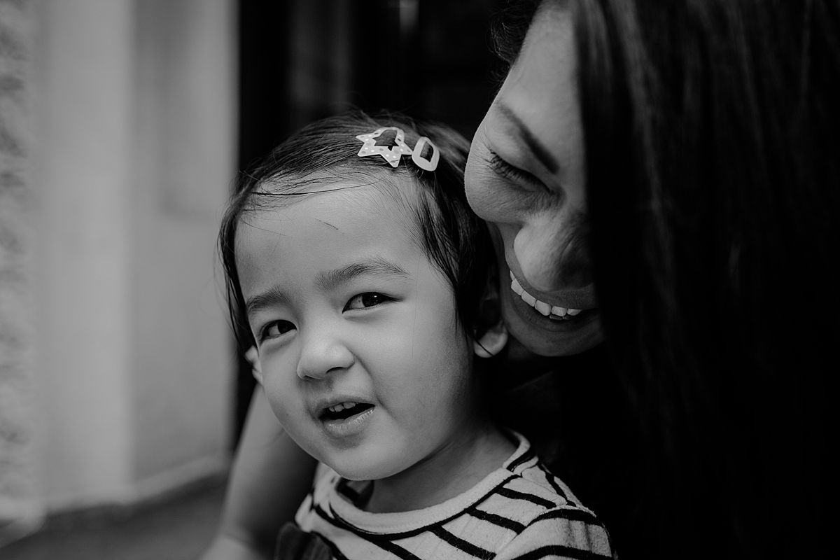 daughter sits on moms lap on nyc stoop in upper manhattan and mom has the hugest smile on her face. krystil mcdowall captures image in nyc documentary lifestyle session family and newborn photographer