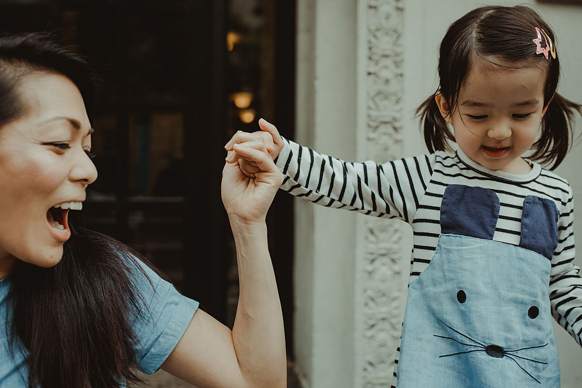 daughter and mom play together on balmy afternoon in front of nyc apartment block. capturing childhood moments