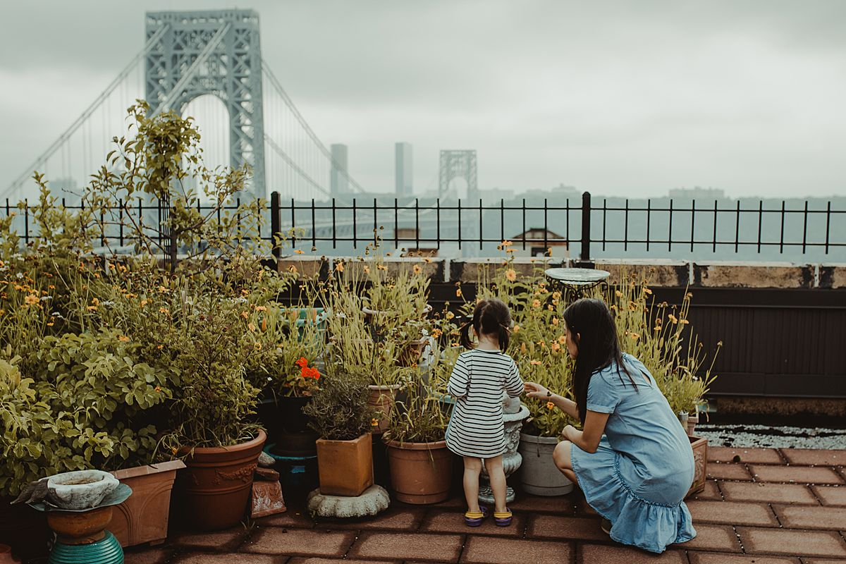 mom and daughter talk about the rooftop potplants while dressed in matching blue dresses on sunny nyc afternoon