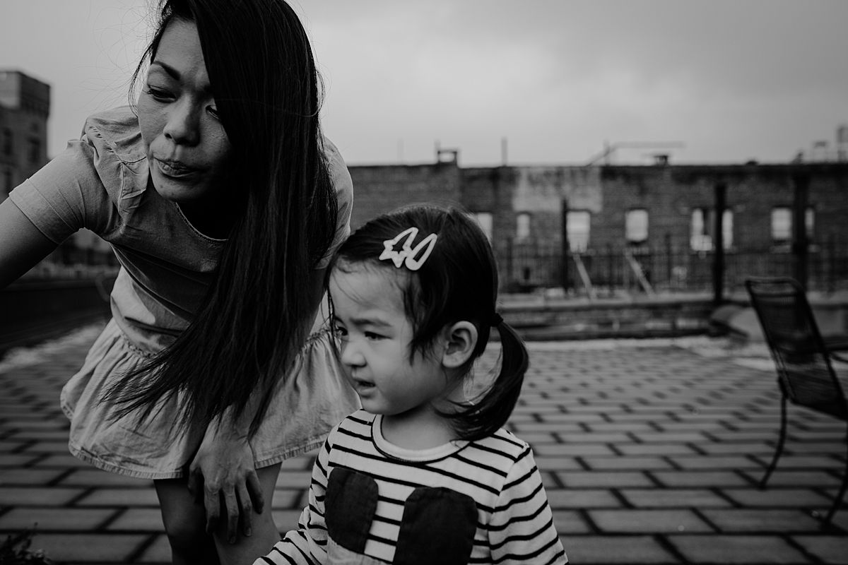 fun family photo shoot. mom and daughter discuss rooftop plants on sunny nyc afternoon outdoor session