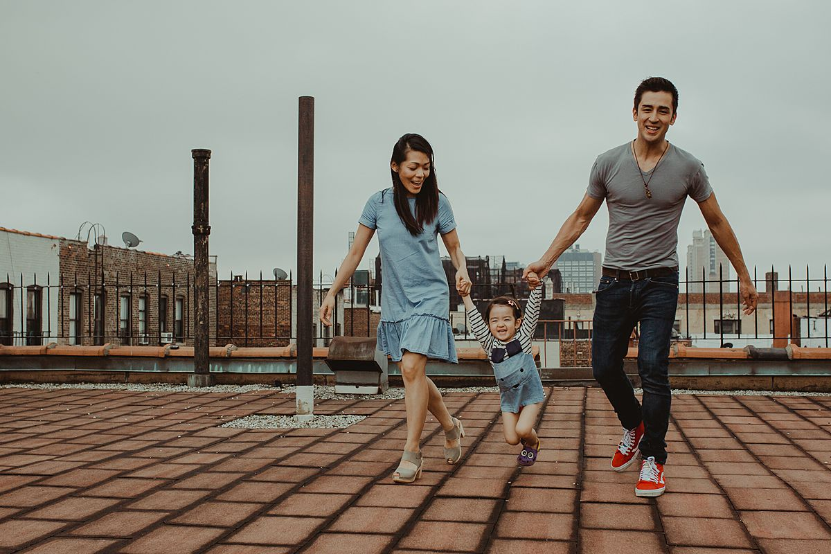 mom, dad and daughter playing games on nyc rooftop with daughter swinging in the air