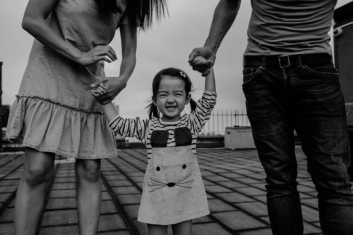 """close up of daughter saying """"cheese"""" while holding mom and dad's hands on nyc rooftop. image by krystil mcdowall photography"""
