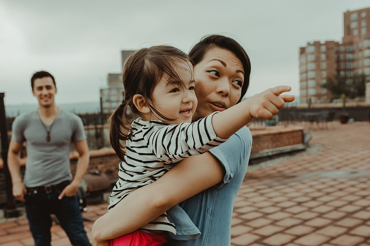 mom and daughter hold each other while daughter points to potplants and dad stands in the distance looking lovingly during documentary family session in nyc