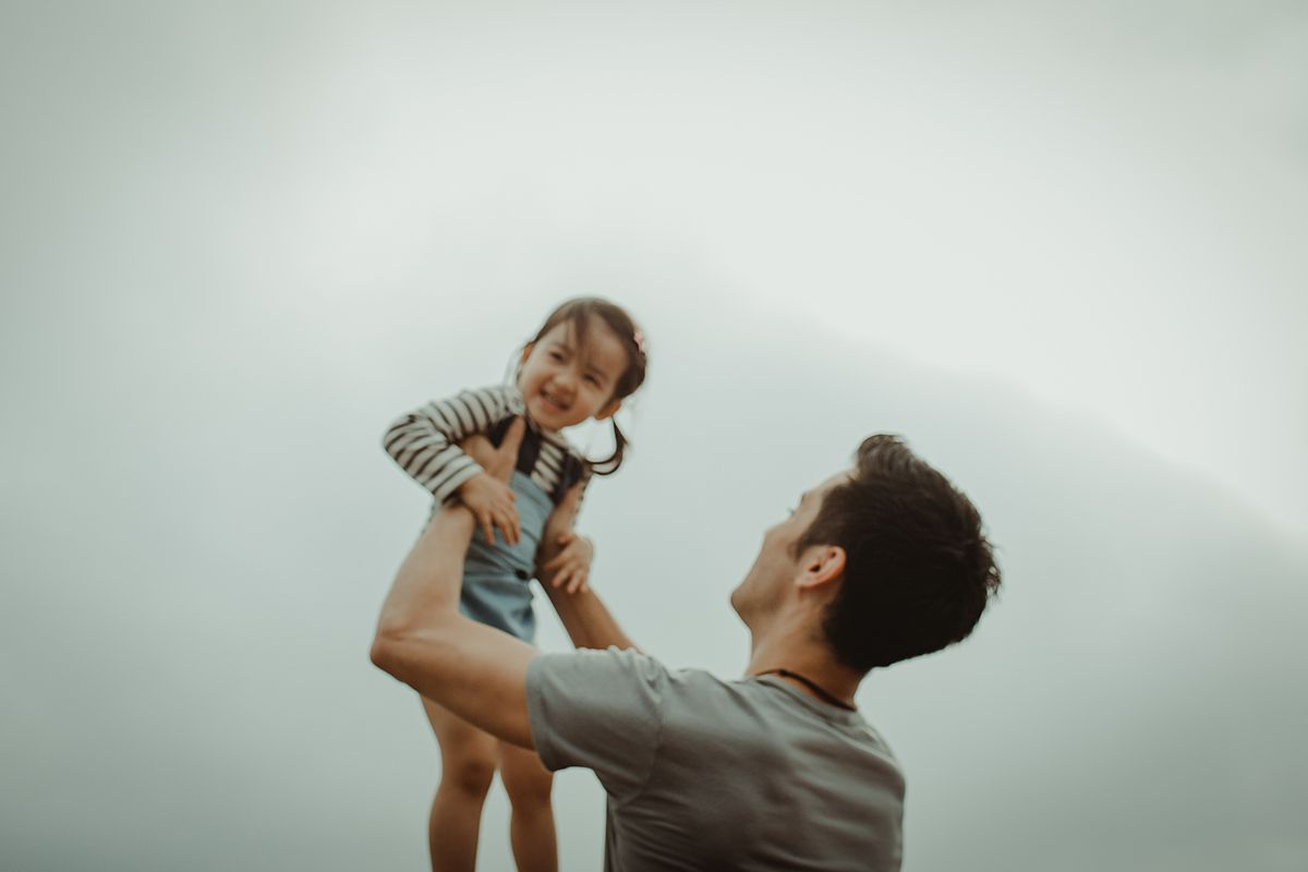 Dad holding daughter in the air. photo taken by nyc family and newborn photographer