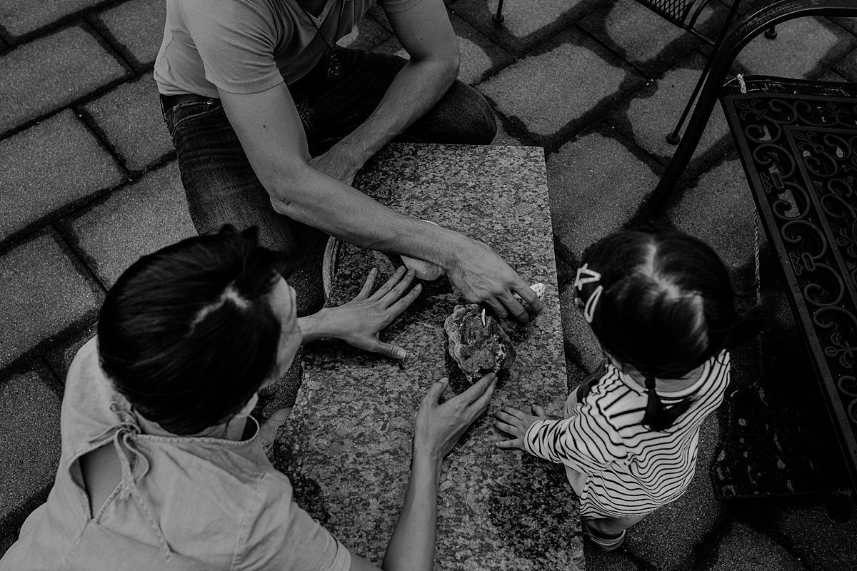 daughter, mom and dad explore beach coral. photo taken from a birds eye view. photo taken by krystil mcdowall during documentary nyc family photoshoot