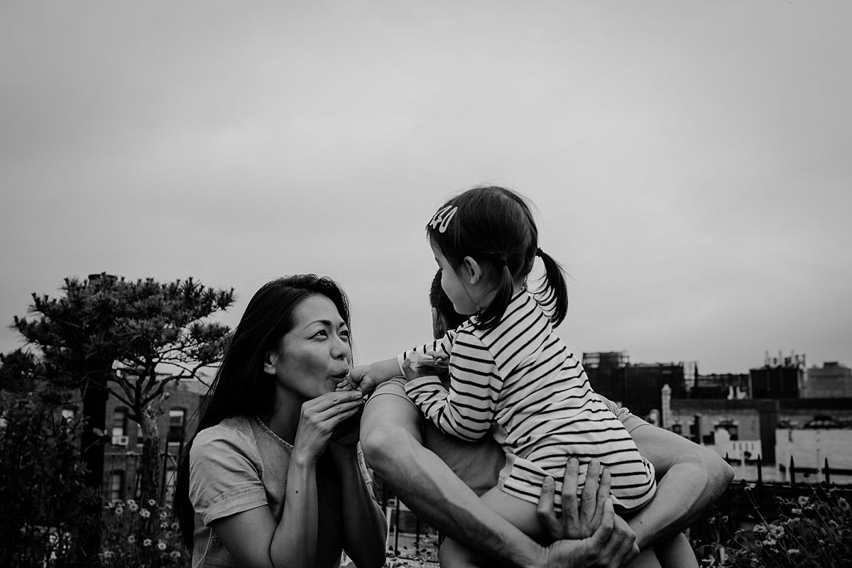mom kisses daughter's hand while daughter enjoys piggy back from dad.image by krystil mcdowall photography in nyc family photoshoot