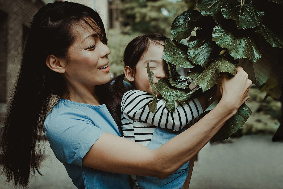 mom and daughter place with tree leaves on nyc sidewalk during documentary family session in nyc. Photo by Krystil McDowall Photography