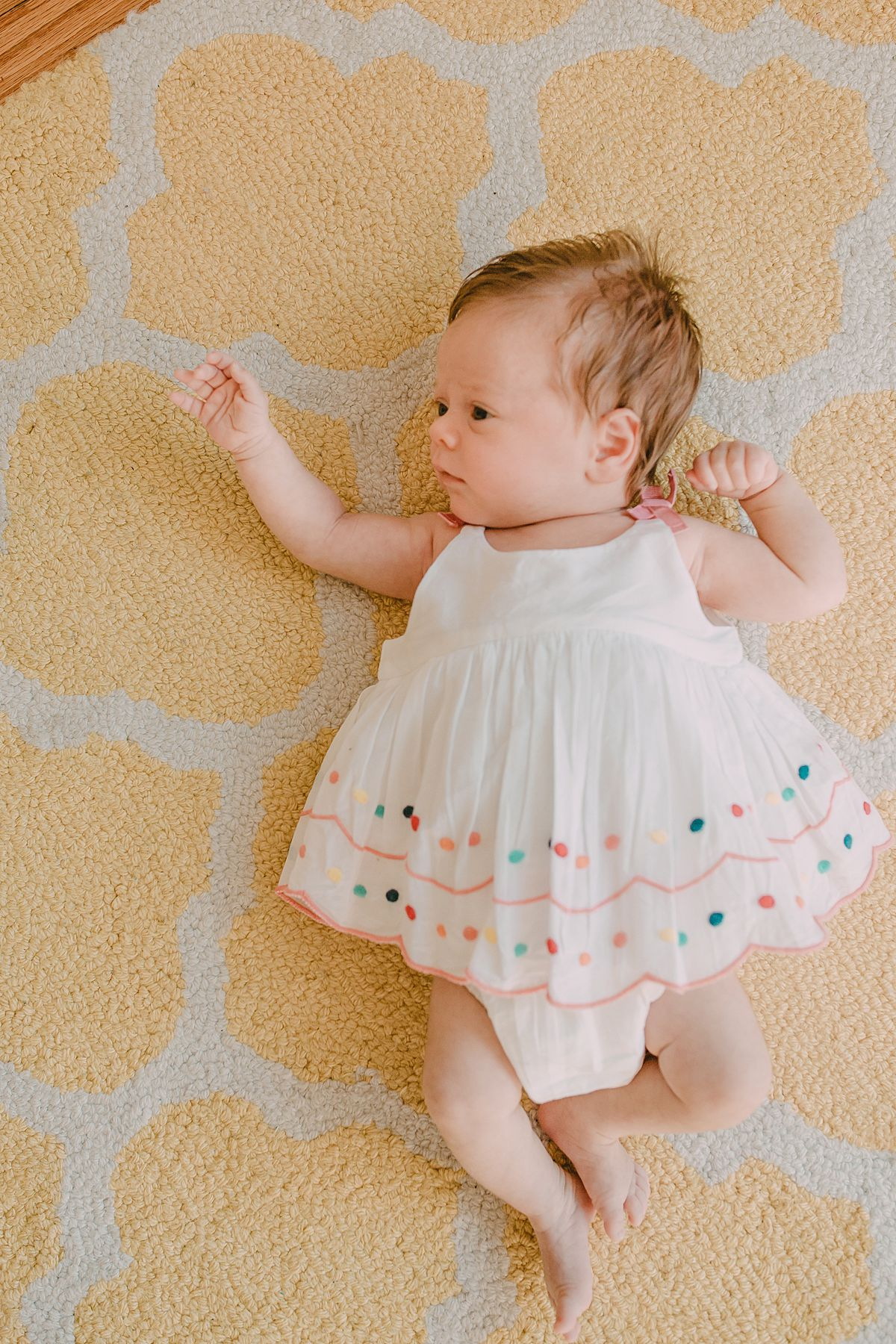 close up of newborn baby girl lying on yellow and white rug in beautiful white and polka dot dress