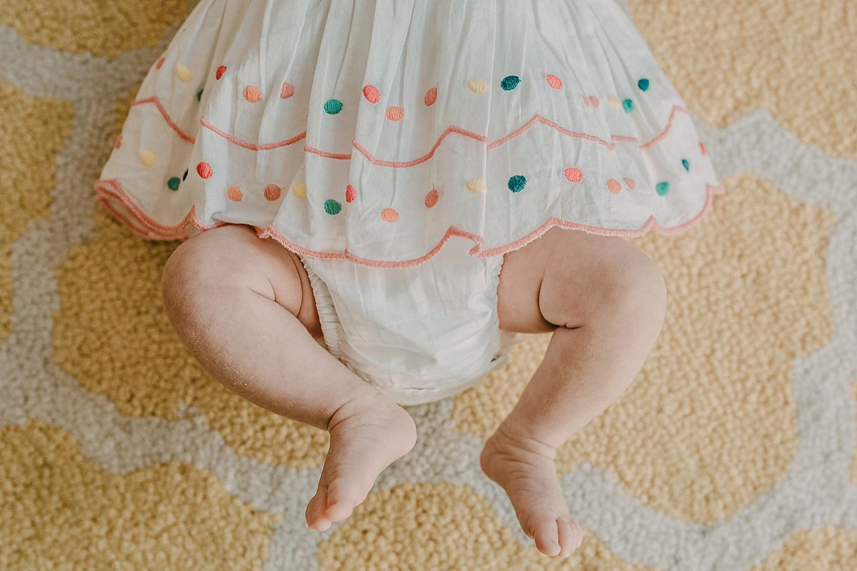 newborn baby girl lying on rug during nyc newborn session and close up of baby feet. Image by krystil mcdowall photography