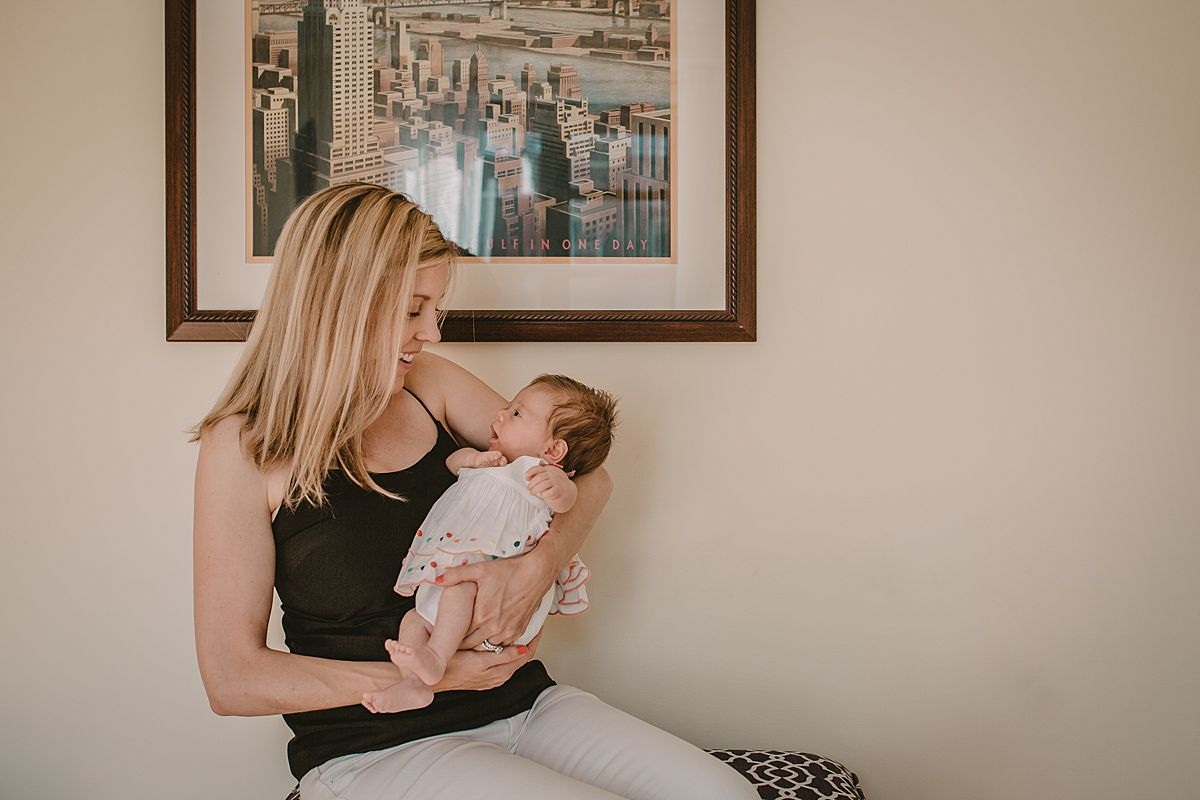 mom holding newborn baby girl sitting in front of nyc sign in family lifestyle session by nyc family and newborn photographer
