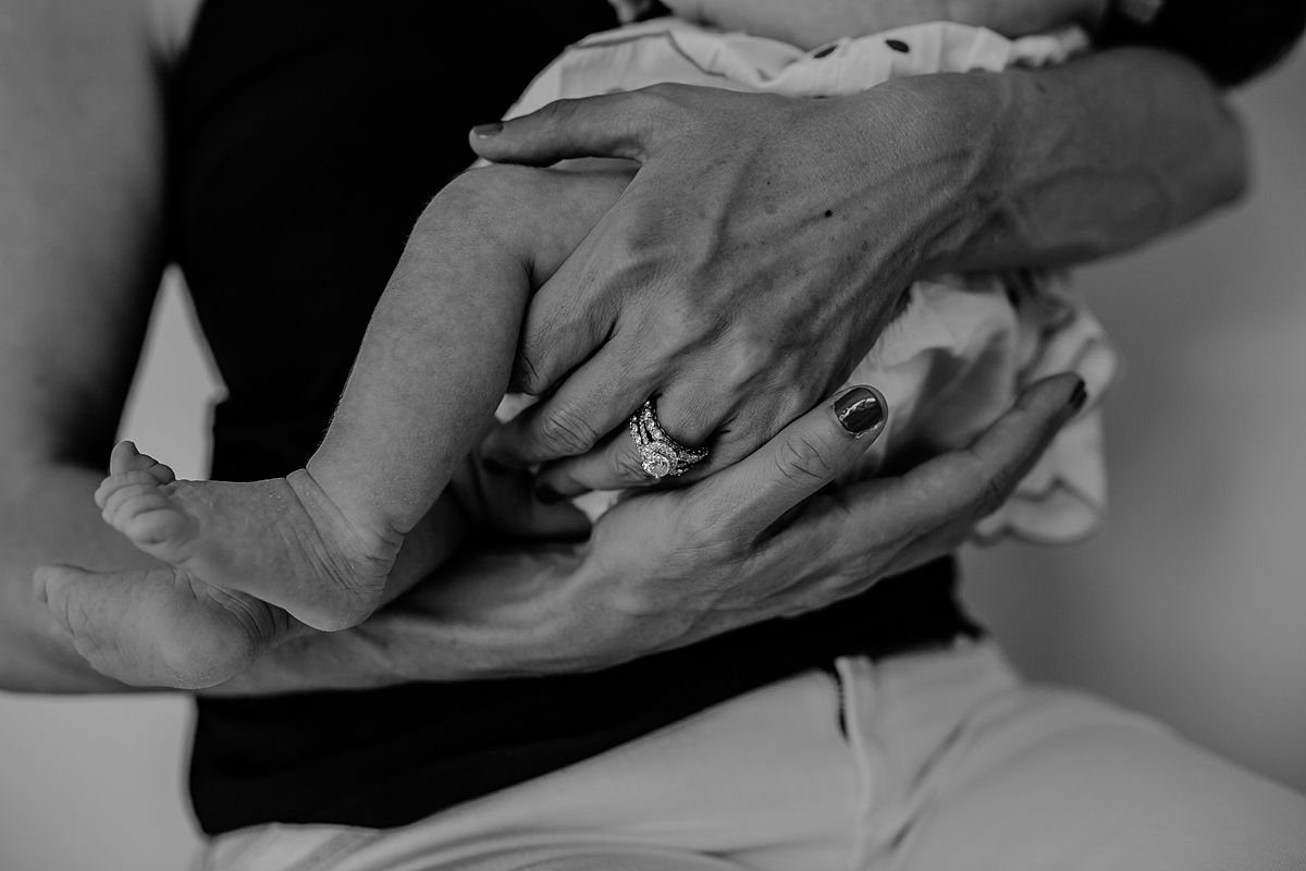 black and white image of newborn girl feet as they dangle while mom holds her. image by krystil mcdowall photography