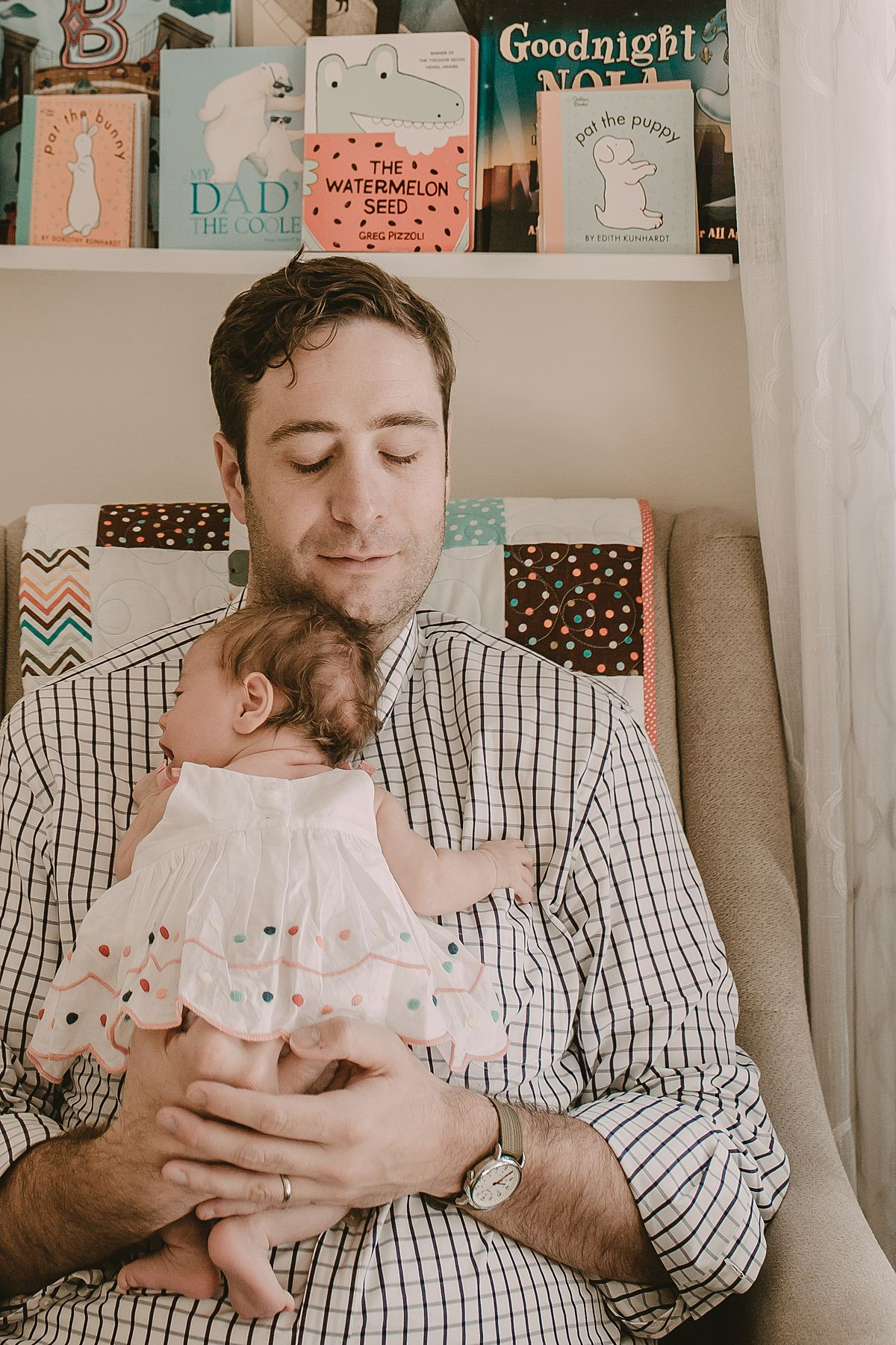 dad holding newborn baby girl enjoying a quiet moment in the rocking chair during documentary session by nyc family and newborn photographer