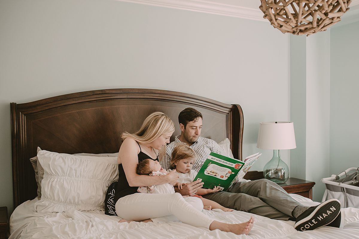 dad, mom, son and daughter reading stories on mom and dad's bed in nyc family lifestyle session