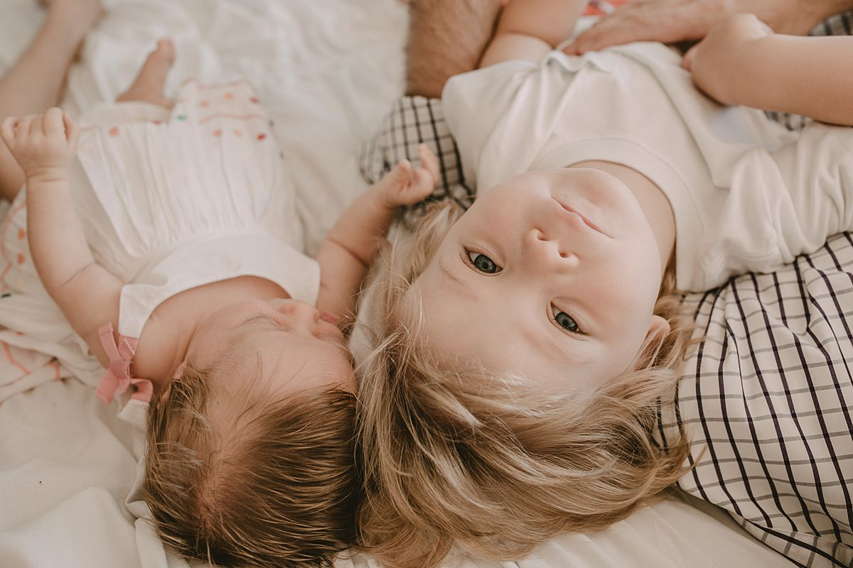 big brother and newborn sister lying on the bed with big brother looking at the camera. nyc newborn session. Image by nyc family and newborn photographer krystil mcdowall