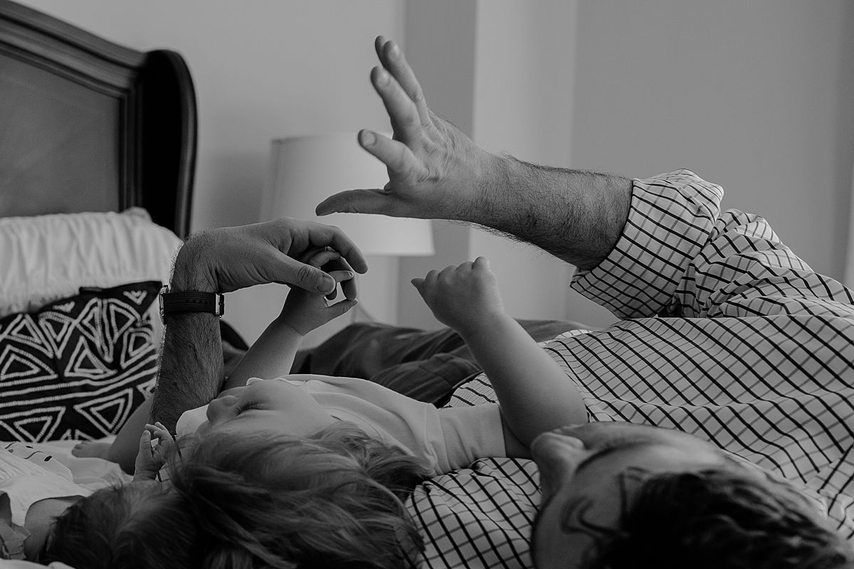 dad and son lying on the bed playing shdow puppets. documentary nyc newborn session by krystil mcdowall