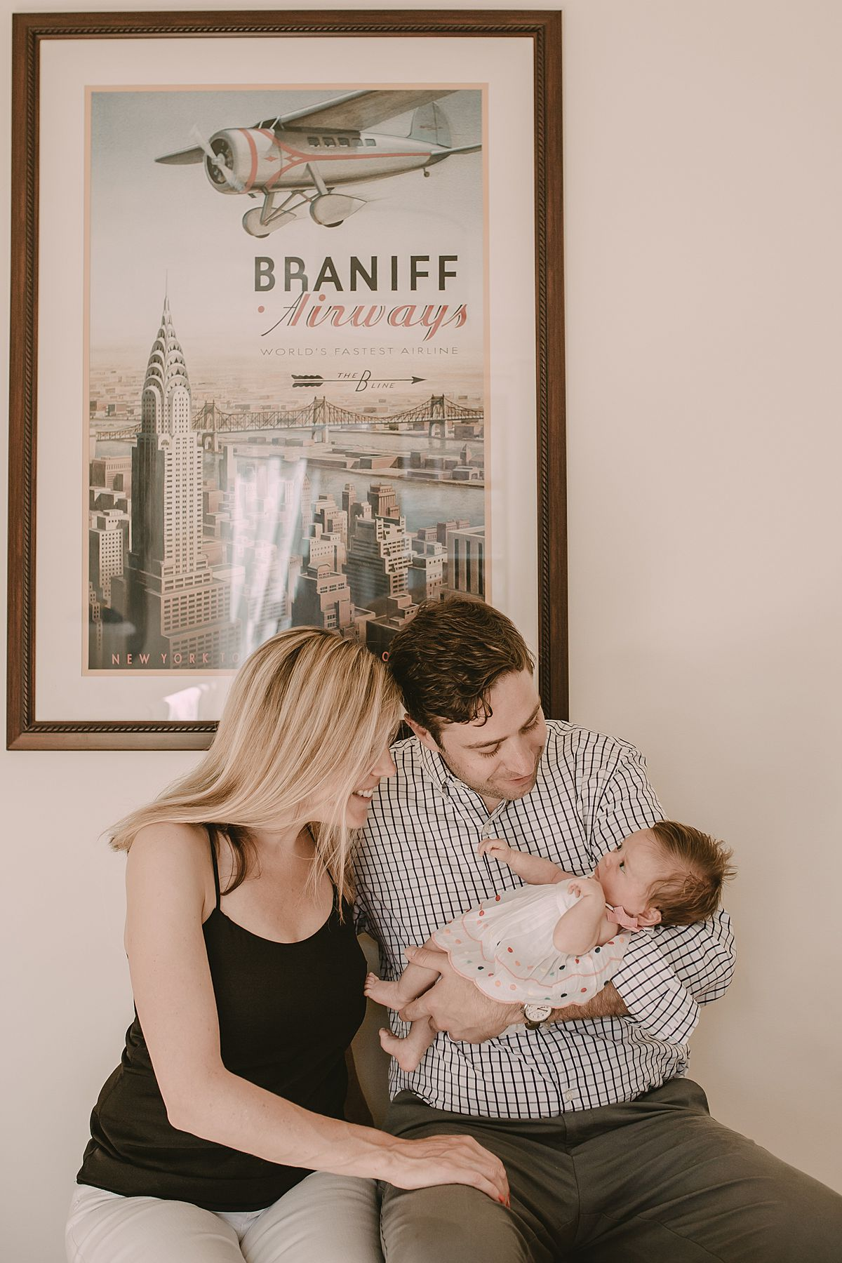 mom and dad looking at newborn daughter with lots of love and smiles and in front of nyc wall hanging. Fun nyc newborn session by krystil mcdowall