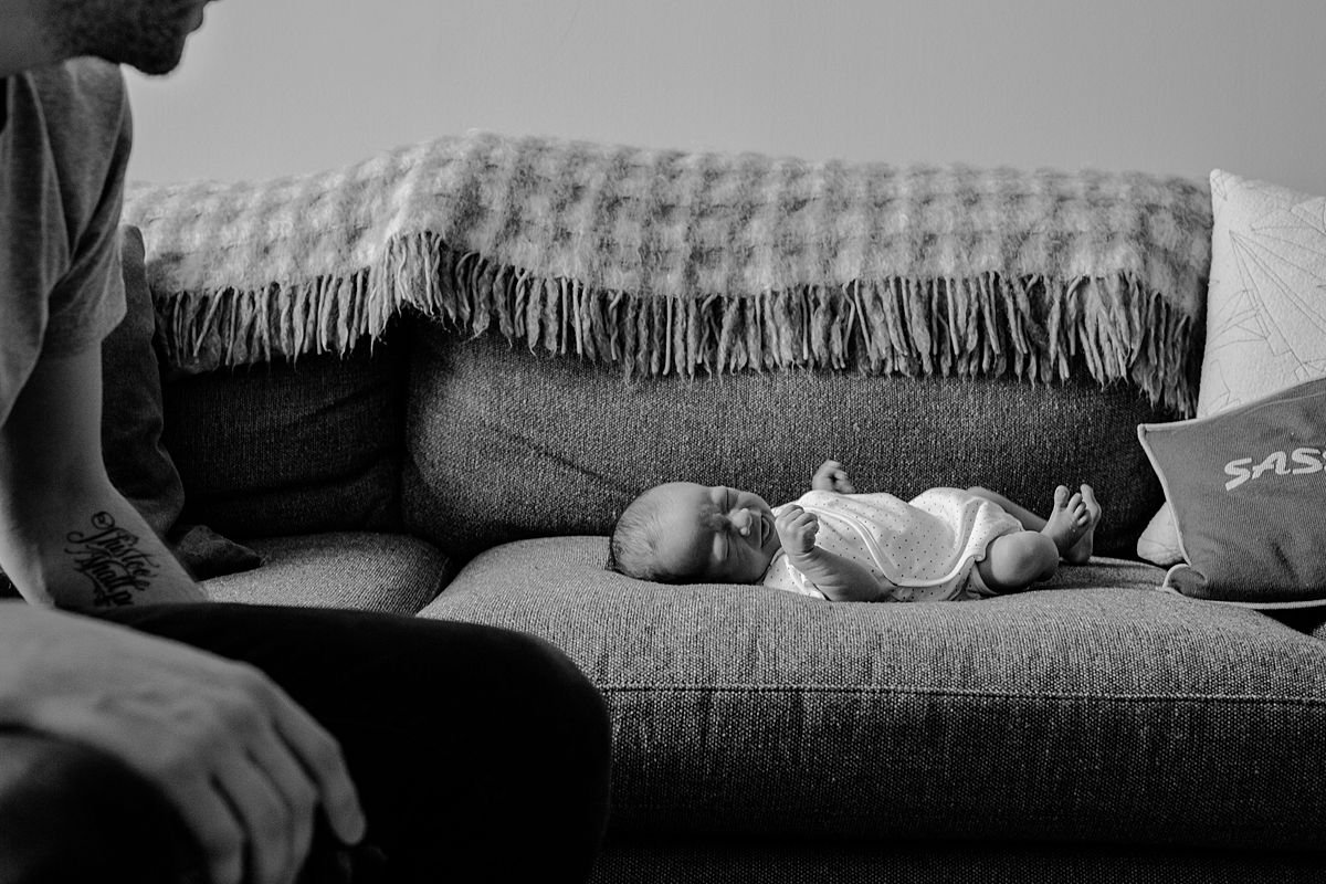 newborn boy scrunches his nose while laying on couch in nyc family newborn session in downtown manhattan