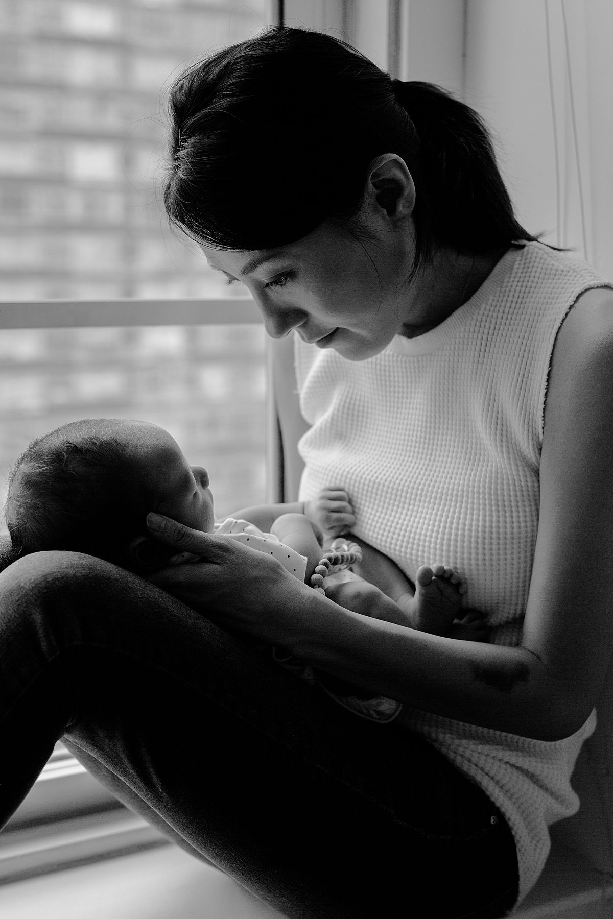 black and white image of mom holding newborn son in lap while sitting on dun drenched window sill. image taken in nyc apartment by nyc family and newborn photographer krystil mcdowall