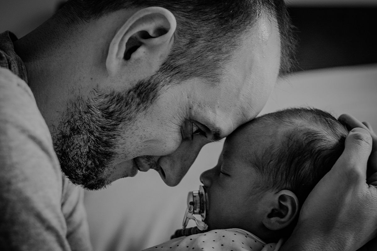 close up black and white image of dad holding newborn son with foreheads touching. photo by nyc family and newborn photographer krystil mcdowall