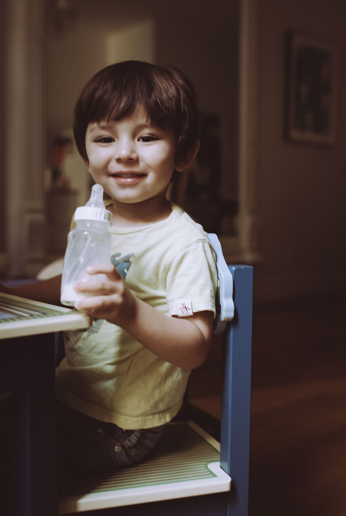 portrait of boy sitting at the table drinking a bottle of milk. photo by nyc family and newborn photographer krystil mcdowall