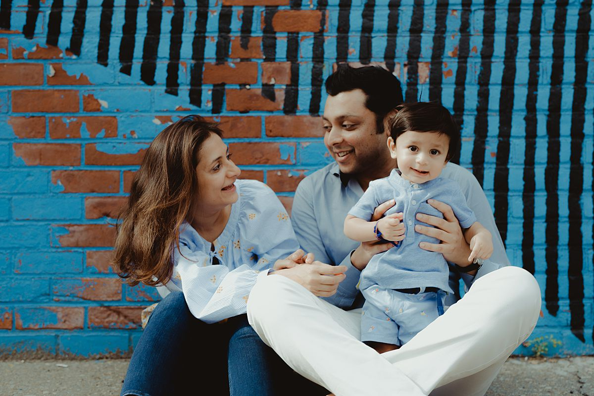 family portrait in front of blue graffiti wall in brooklyn nyc. image by nyc family and newborn photographer krystil mcdowall