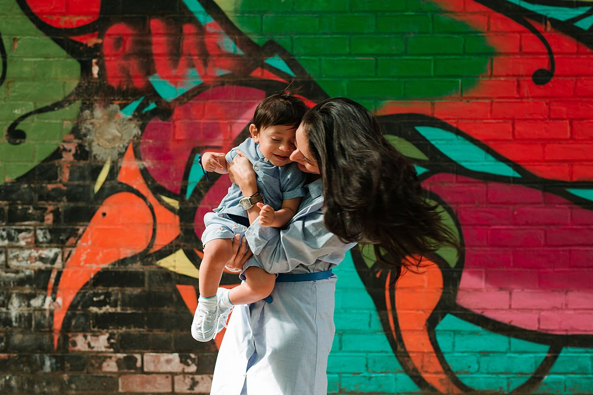 photo of son and aunty playing fun spin games in front of colorful graffiti wall in dumbo