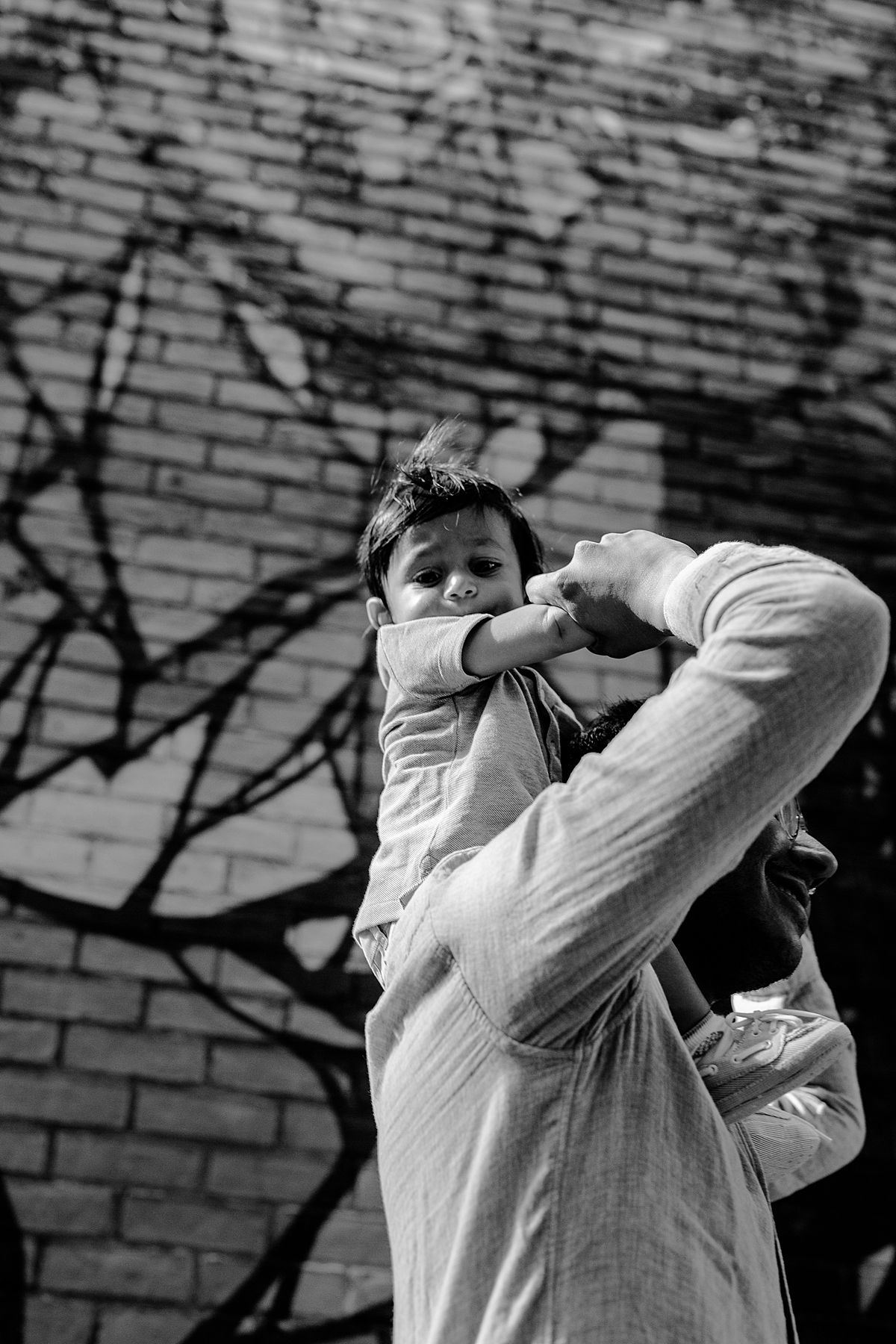 black and white photo of nephew having a shoulder ride with uncle in dumbo brooklyn. photo by nyc family and newborn photographer krystil mcdowall