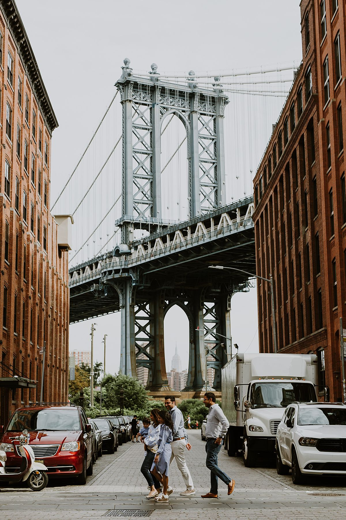 family photo walking in front of the manhattan bridge in dumbo brooklyn. photo by krystil mcdowall photography