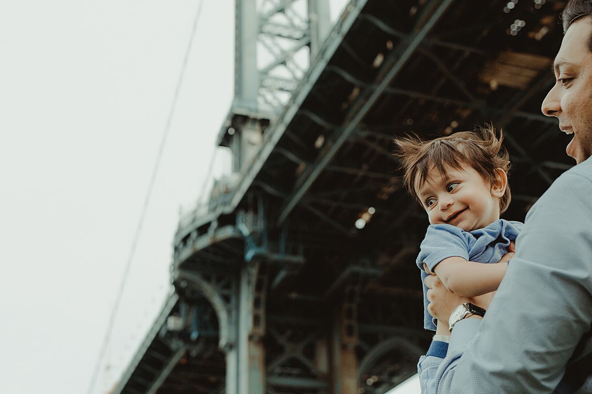 dad holds son in front of manhattan bridge in dumbo during fun family sessions. photo by krystil mcdowall photography
