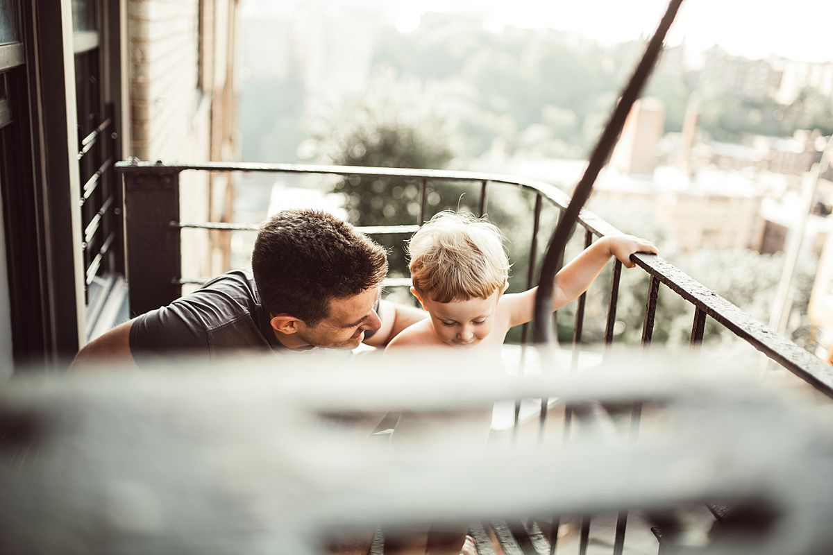 dad and son together on fire escape outside of nyc apartment. image by nyc family and newborn photographer krystil mcdowall
