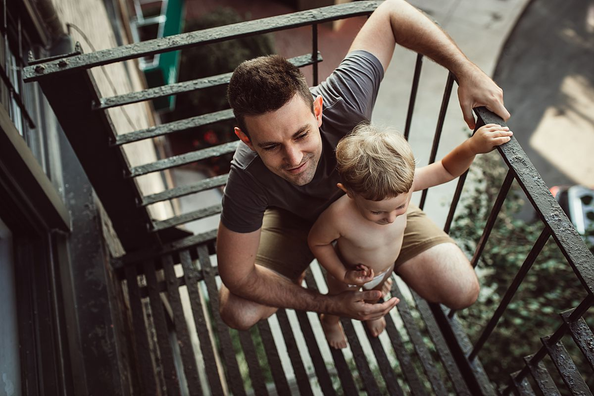 almost bird's eye view of dad and son on fire escape in documentary family lifestyle session with krystil mcdowall